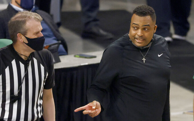 Tulane head coach Ron Hunter, right, talks with a game official as Tulane plays Houston during the second half of an NCAA college basketball game in the quarterfinal round of the American Athletic Conference men's tournament Friday, March 12, 2021, in Fort Worth, Texas. (AP Photo/Ron Jenkins)