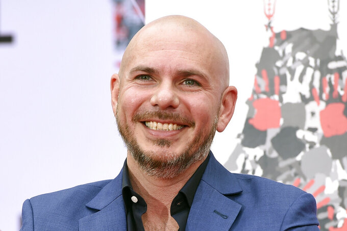 "FILE - Pitbull smiles during a hand and footprint ceremony at the TCL Chinese Theatre in Los Angeles, in this Friday, Dec. 14, 2018, file photo. NASCAR is being heavily promoted by a broadcast partner as about to embark on ""The Best Season Ever"" and on paper that could be true. NASCAR this year will race on dirt for the first time since 1970, the schedule includes a whopping seven road courses and five venues new to the Cup Series. Michael Jordan and Pitbull are among new team owners entering the sport in 2021 and Chase Elliott, NASCAR's most popular driver, is the reigning champion.  (Photo by Chris Pizzello/Invision/AP, File)"