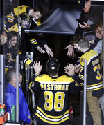 Fans reach to congratulate Boston Bruins right wing David Pastrnak (88) who scored four goals in an NHL hockey game against the Anaheim Ducks, Monday, Oct. 14, 2019, in Boston. (AP Photo/Elise Amendola)