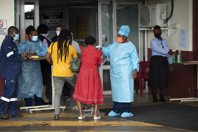 A health worker checks the temperature of an elderly patient at the emergency entrance of the Steve Biko Academic Hospital in Pretoria, South Africa, Monday, Jan. 11, 2021, which is battling an ever-increasing number of COVID-19 patients. (AP Photo/Themba Hadebe)