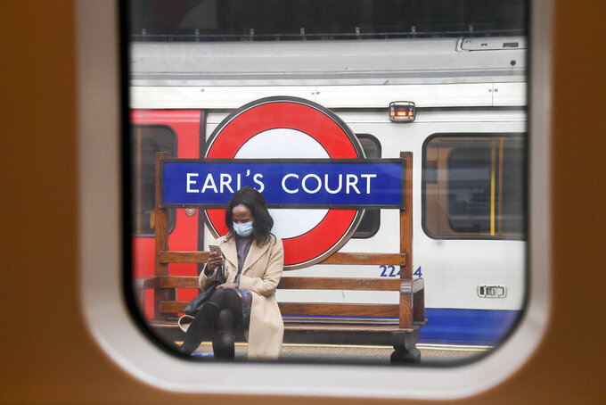 A woman sits on a bench at Earl's Court underground station, wearing a mask as the lockdown due to the coronavirus outbreak continues, in London, Thursday, April 30, 2020. (AP Photo/Alberto Pezzali)