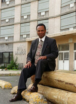 In this May 15, 1999 photo, Donald Bernard Sr., chairman of the African American Heritage Parade, poses outside of the defunct Hill Manor where he once lived in Newark, N.J. As a Democratic presidential candidate, Booker has leaned heavily on his record as Newark mayor. But the watershed scandal still burns some of his critics in New Jersey. Bernard Sr., pleaded guilty to accepting $957,000 from contractors for help getting them work. (Samir Id-Deen/NJ Advance Media via AP)