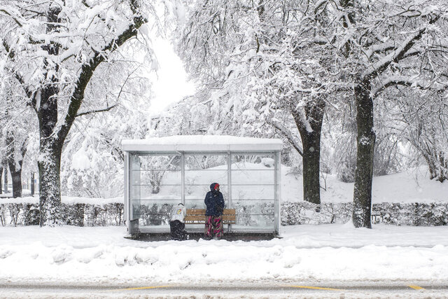 A woman waits at a bus stop in Zurich, Switzerland, Friday, Jan. 15, 2021. The traffic situation is difficult after persistent snowfalls in eastern Switzerland. (Ennio Leanza/Keystone via AP)