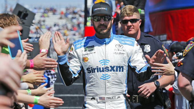 NASCAR Cup Series driver Martin Truex Jr. (19) greets fans during driver introductions prior to the NASCAR Cup Series auto race at the Martinsville Speedway in Martinsville, Va., Sunday, March 24, 2019. (AP Photo/Steve Helber)