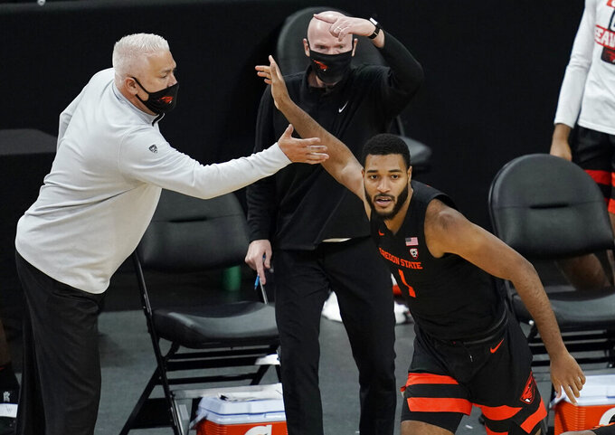 Oregon State head coach Wayne Tinkle celebrates after Maurice Calloo, right, scored a 3-point shot against Oregon during the second half of an NCAA college basketball game in the semifinal round of the Pac-12 men's tournament Friday, March 12, 2021, in Las Vegas. (AP Photo/John Locher)