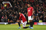 Manchester United's Anthony Martial stands next to kneeling teammate and substitute player Marcus Rashford after he sustained an injury during the English FA Cup third round replay soccer match between Manchester United and Wolverhampton Wanderers at Old Trafford in Manchester, England, Wednesday, Jan. 15, 2020. (AP Photo/Rui Vieira)