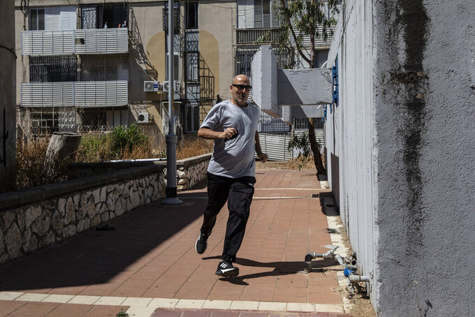 An Israeli runs for cover in Ashdod, Israel during sirens warning of incoming rockets fired from Gaza Strip, Tuesday, May 18, 2021. (AP Photo/Heidi Levine)