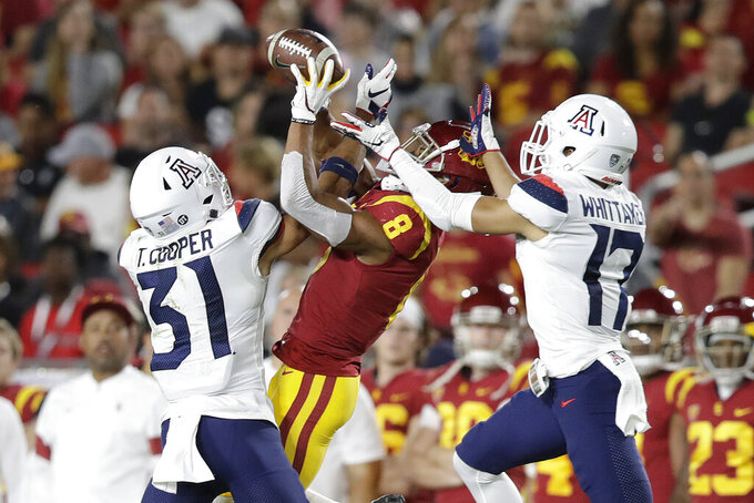 Arizona safety Tristan Cooper (31) and cornerback Jace Whittaker (17) break up a pass intended for Southern California wide receiver Amon-Ra St. Brown (8) during the first half of an NCAA college football game Saturday, Oct. 19, 2019, in Los Angeles. (AP Photo/Marcio Jose Sanchez)