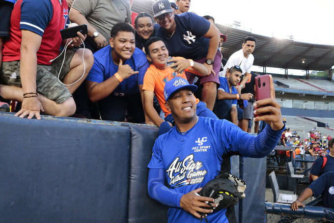 """FILE - In this Jan. 11, 2020, file photo, Kansas City Royals' Salvador Perez takes a photograph with a fan's cellphone prior to an All-Star exhibition softball game at Rod Carew stadium in Panama City, Panama. When the virus wanes enough to allow the games to begin again, the very essence of these events will likely be missing.  """"You know how much I love to talk to the fans, you know? To be in conversation, to throw the ball to kids,"""" Kansas City Royals catcher Salvador Perez said. (AP Photo/Eric Batista, File)"""