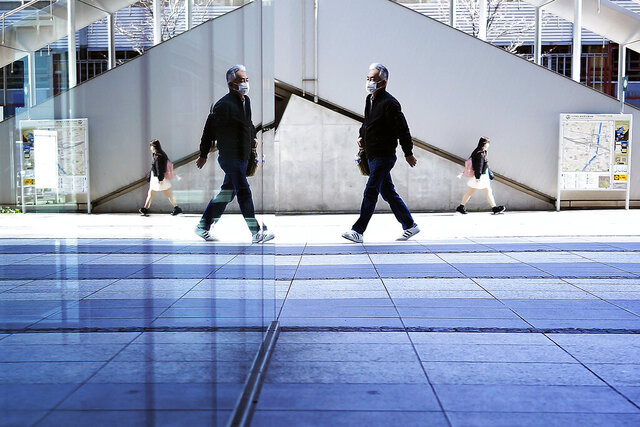 People with protective mask walk in Tokyo, Monday, Feb. 24, 2020. Most of Japan's cases were from the Diamond Princess cruise ship, where nearly one-fifth of its 3,711 passengers and crew became infected. (AP Photo/Eugene Hoshiko)
