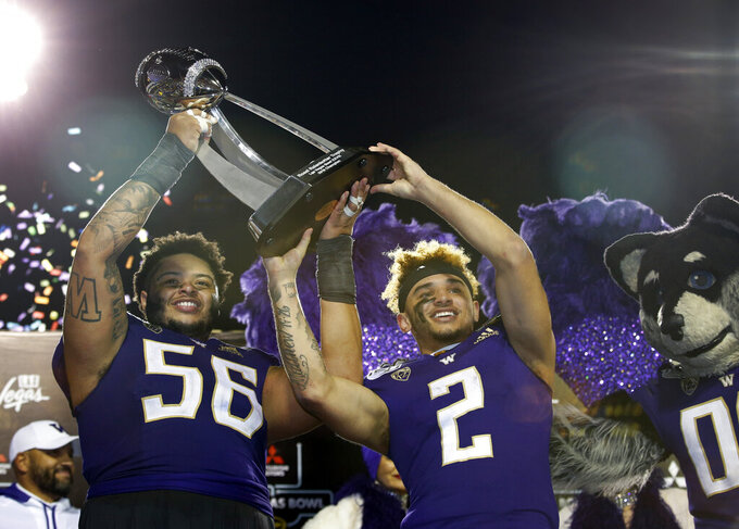 Washington offensive lineman Nick Harris (56) and wide receiver Aaron Fuller (2) pose with the trophy after defeating Boise State in the Las Vegas Bowl NCAA college football game at Sam Boyd Stadium, Saturday, Dec. 21, 2019, in Las Vegas. (AP Photo/Steve Marcus)