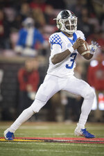 Kentucky quarterback Terry Wilson (3) scrambles with the ball during the first half of the team's NCAA college football game against Louisville in Louisville, Ky., Saturday, Nov. 24, 2018. (AP Photo/Bryan Woolston)