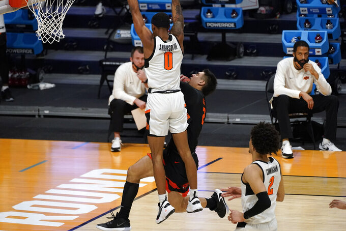 Oklahoma State guard Avery Anderson III (0) fouls Oregon State guard Jarod Lucas (2) during the first half of a men's college basketball game in the second round of the NCAA tournament at Hinkle Fieldhouse in Indianapolis, Sunday, March 21, 2021. (AP Photo/Paul Sancya)