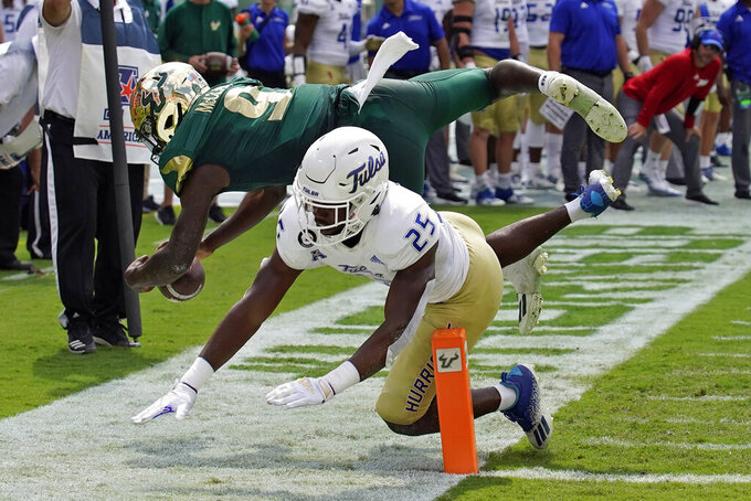 South Florida quarterback Timmy McClain (9) is upended by Tulsa safety Jaise Oliver (25) after a run during the first half of an NCAA college football game Saturday, Oct. 16, 2021, in Tampa, Fla. (AP Photo/Chris O'Meara)