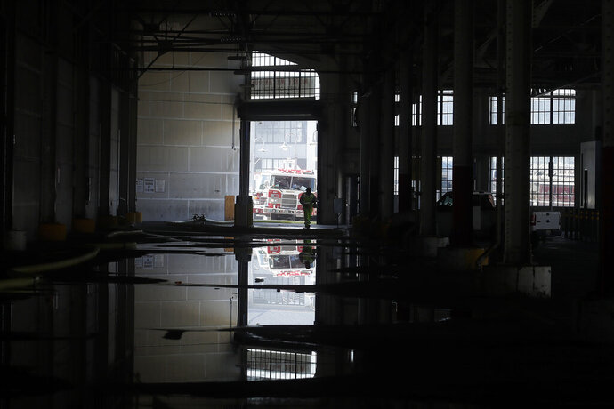 A fire official is shown reflected in a puddle in a warehouse after a fire broke out before dawn at Fisherman's Wharf in San Francisco, Saturday, May 23, 2020. Fire officials said no injuries have been reported Saturday morning and firefighters are making multiple searches to ensure no one was inside the building on Pier 45. (AP Photo/Jeff Chiu)