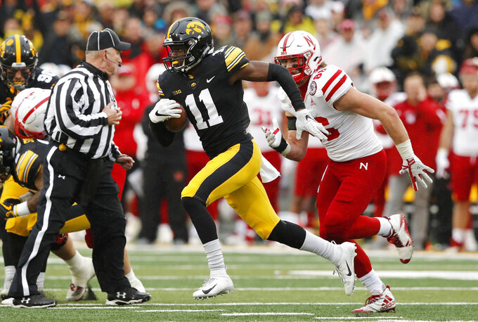 Iowa defensive back Michael Ojemudia (11) runs from Nebraska tight end Jack Stoll, right, after intercepting a pass during the second half of an NCAA college football game, Friday, Nov. 23, 2018, in Iowa City, Iowa. Iowa won 31-28. (AP Photo/Charlie Neibergall)