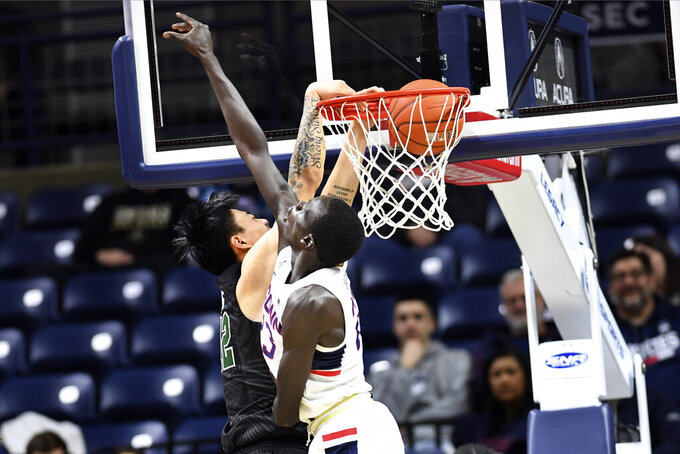 Tulane's Kevin Zhang (12) shoots over Connecticut's Akok Akok (23) in the first half of an NCAA college basketball game Wednesday, Jan. 8, 2020, in Storrs, Conn. (AP Photo/Stephen Dunn)