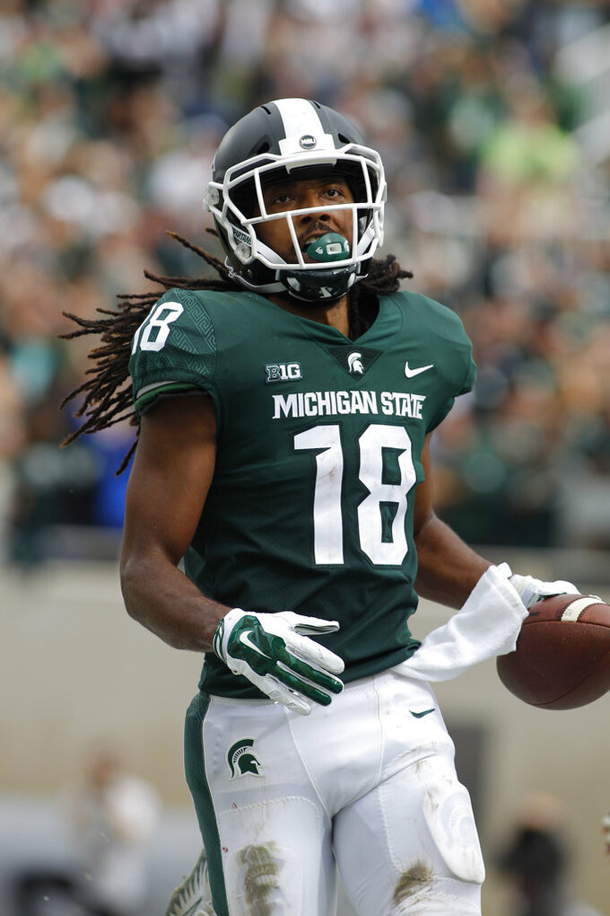 FILE - In this Saturday, Oct. 6, 2018, file photo, Michigan State's Felton Davis scores on a 48-yard run against Northwestern during the third quarter of an NCAA college football game in East Lansing, Mich.  Davis took the ball on a double reverse, cut inside and ran 48 yards for a touchdown in a 29-19 loss to Northwestern. (AP Photo/Al Goldis, File)