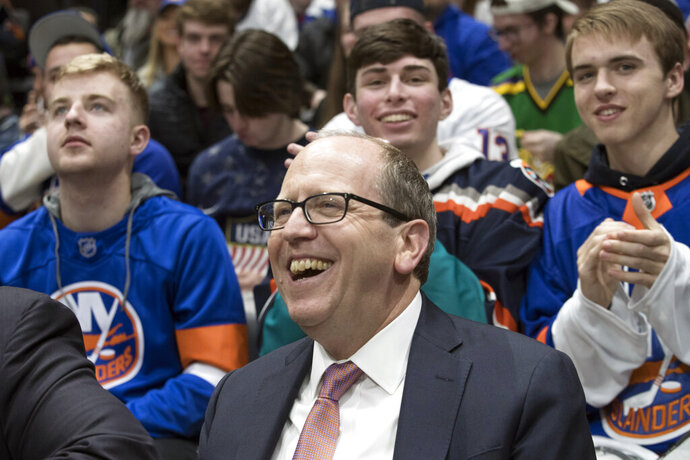 FILE - In this Thursday, March 14, 2019, file photo, Jon Ledecky, majority owner of the New York Islanders, watches NHL hockey game action during the second period against the Montreal Canadiens, in Uniondale, N.Y. The New York Islanders have reached a 20-year naming rights deal for their new arena with wealth management service UBS. The facility on the grounds of the Belmont Park racetrack will be called UBS Arena at Belmont Park. It's projected to open in time for the 2021-22 NHL season. (AP Photo/Mary Altaffer, File)