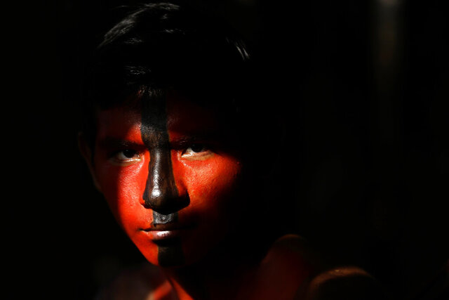 Tenetehara Indigenous Jair Tembe eyes the camera during a festival at the Alto Rio Guama Indigenous Territory, near Paragominas, in the Brazilian state of Para, Brazil, Monday, Sept. 7, 2020. The Indigenous group, also known as Tembe, held a festival during the week to celebrate and give thanks that none of their members have fallen ill during the new coronavirus pandemic, after closing their area off in March. (AP Photo/Eraldo Peres)