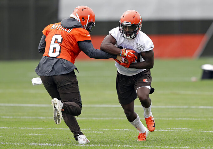 Cleveland Browns quarterback Baker Mayfield, left, hands the ball off to running back D'Ernest Johnson during an NFL football organized team activity session at the team's training facility, Thursday, May 30, 2019, in Berea, Ohio. (AP Photo/Tony Dejak)