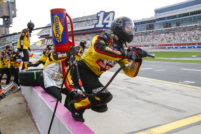 The pit crew of Clint Bowyer (14) jumps over the wall for a pit stop in a NASCAR Cup Series auto race at Charlotte Motor Speedway in Concord, N.C., Sunday, Oct. 11, 2020. (AP Photo/Nell Redmond)