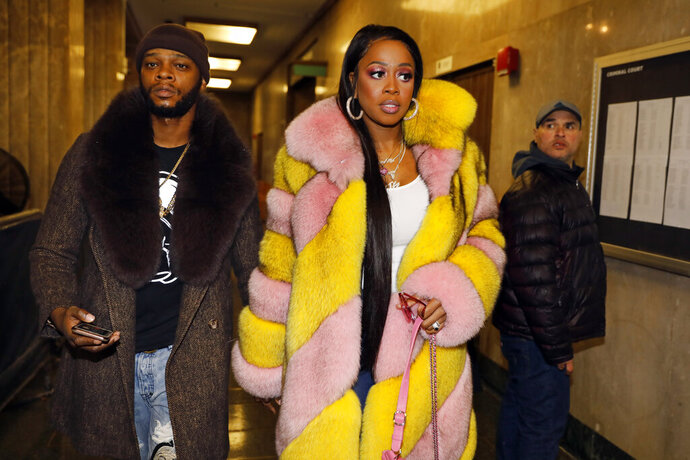 Rapper Remy Ma, whose real name is Reminisce Smith, leaves Manhattan criminal court, with husband Shamele Mackie, whose stage name is Papoose, in New York, Monday, Dec. 2, 2019. She's accused of punching her