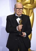 FILE - In this Sunday, Feb. 28, 2016 file photo, Italian composer Ennio Morricone poses in the press room with the award for best original score for