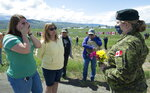 Royal Canadian Air Force Public Affairs Officer Lt. Alexandra Hejduk, right, speaks with retired nurse Dana Hings, center, and her daughter Jenna Phillips at the Kamloops airport in Kamloops, British Columbia, Monday, May 18, 2020. Hings and Phillips were first on the scene to attend to Canadian Forces Snowbirds Capt. Jenn Casey, who died on Sunday after the jet she was in crashed after takeoff. (Jonathan Hayward/The Canadian Press via AP)