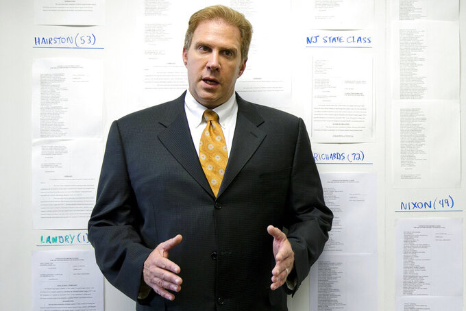 FILE - In this July 18, 2014, file photo, lawyer Craig Mitnick speaks as he stands in front of a photograph that lists some of the approximately 1,400 players in NFL concussion litigation he represented, in Haddonfield, N.J. After several years of infighting over $112 million in legal fees in the NFL concussion case, a federal appeals court has approved a plan to give nearly half the money to New York-based Seeger Weiss. The decision Thursday, May 7, 2020, grants New York-based Seeger Weiss firm over $51 million, more than 10 times the amount of any other firm, including the lawyers who filed the first cases in 2012. Mitnick, whose split of the legal fees was left at about $675,000, felt the appeals court did not sufficiently explain its reasoning. Oral arguments in the case were cancelled amid the COVID-19 courthouse shutdown, he said. (AP Photo/Matt Rourke, File)
