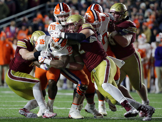 Boston College defensive end Zach Allen, center, helps tackle Clemson running back Adam Choice (26) during the first half of an NCAA college football game Saturday, Nov. 10, 2018, in Boston. (AP Photo/Elise Amendola)