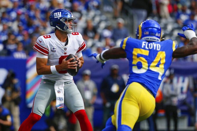New York Giants quarterback Daniel Jones, left, looks to throw under pressure during the first half of an NFL football game against the Los Angeles Rams, Sunday, Oct. 17, 2021, in East Rutherford, N.J. (AP Photo/John Munson)