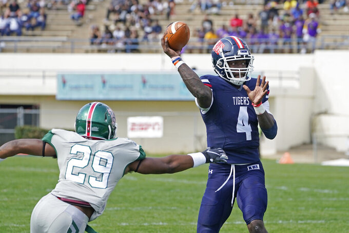 Jackson State quarterback Jalon Jones (4) is pressured by Mississippi Valley State defensive back Kharee Lockley (29) during the first half of an NCAA college football game, Sunday, March 14, 2021, in Jackson, Miss. (AP Photo/Rogelio V. Solis)