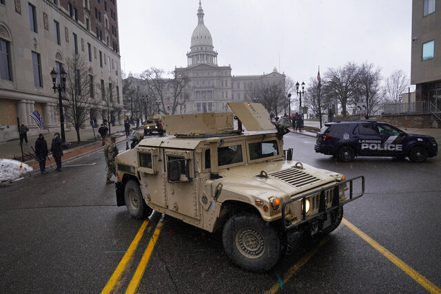Michigan National Guard and Lansing Police Department vehicles block a street outside the state capitol in Lansing, Mich., Sunday, Jan. 17, 2021. (AP Photo/Paul Sancya)