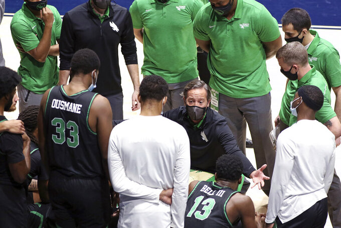North Texas coach Grant McCasland speaks with players during the second half of an NCAA college basketball game against West Virginia, Friday, Dec. 11, 2020, in Morgantown, W.Va. (AP Photo/Kathleen Batten)