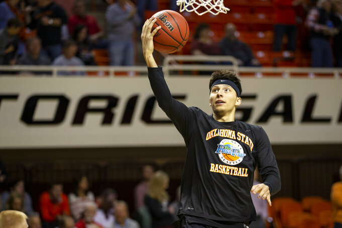 Oklahoma State's Lindy Waters III warms up wearing a shirt honoring the 1995 Oklahoma State Final Four team before Oklahoma State's 73-70 victory over Texas Tech in the NCAA college basketball game NCAA college basketball game in Stillwater, Okla., Saturday, Feb. 15, 2020. (AP Photo/Mitch Alcala)