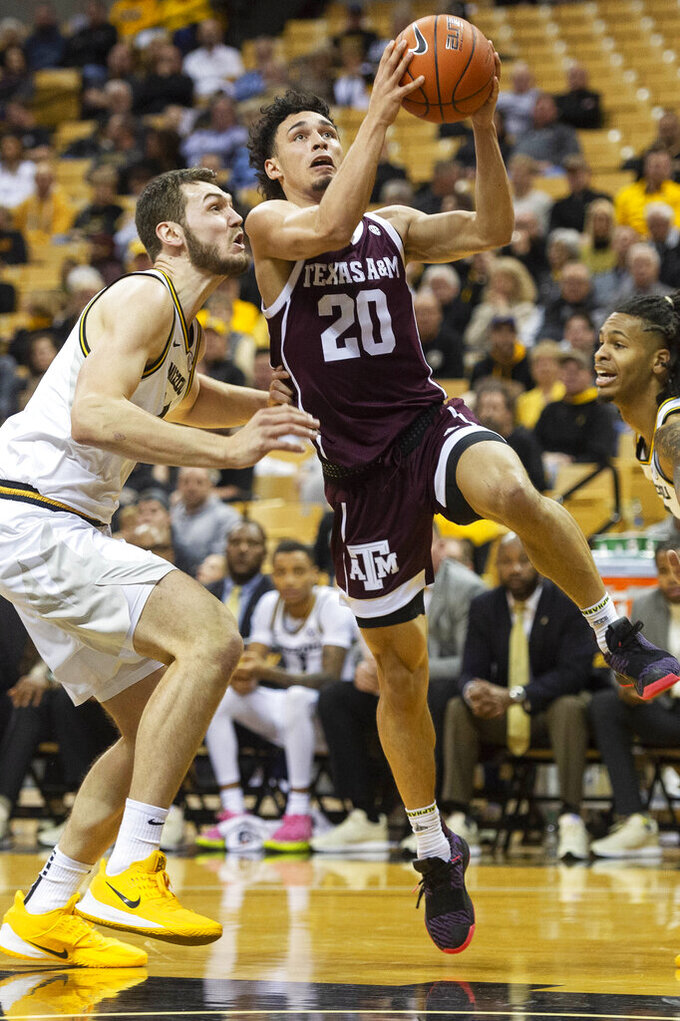 Texas A&M guard Andre Gordon, right, shoots past Missouri forward Reed Nikko, left, during the first half of an NCAA college basketball game Tuesday, Jan. 21, 2020, in Columbia, Mo. (AP Photo/L.G. Patterson)