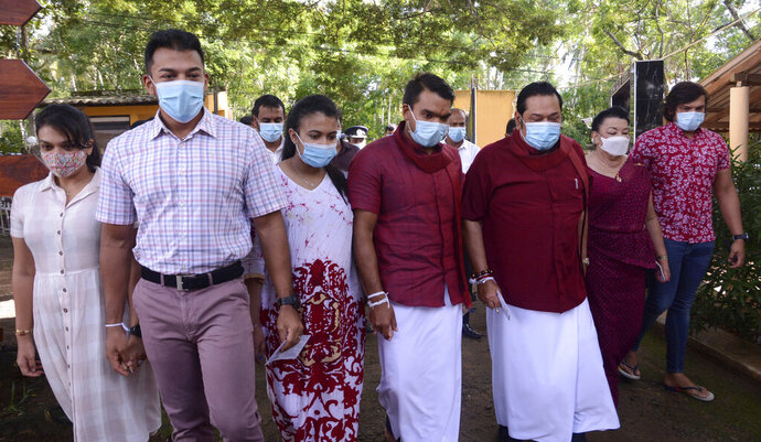 Sri Lankan Prime Minister Mahinda Rajapaksa, third right, his wife Shiranthi, second right, and family members arrive to cast their votes in their home village Madamulana, Sri Lanka, Wednesday, Aug. 5, 2020. Sri Lankans started voting Wednesday to elect a new Parliament that is expected to give strong support to the powerful and popular Rajapaksa brothers. (AP Photo/Pradeep Pathirana)
