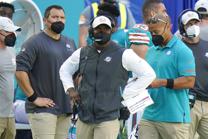 Miami Dolphins head coach Brian Flores, center, look up during the second half of an NFL football game against the New England Patriots, Sunday, Dec. 20, 2020, in Miami Gardens, Fla. (AP Photo/Chris O'Meara)