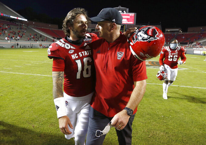 North Carolina State NCAA college football head coach Dave Doeren talks with quarterback Bailey Hockman (16) after beating Duke 31-20 at Carter-Finley Stadium in Raleigh, N.C., Saturday, Oct. 17, 2020. (Ethan Hyman/The News & Observer via AP)