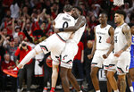 Cincinnati guard Logan Johnson (0) gets a hug from teammate Nysier Brooks, right, as they celebrate the team's 71-69 win over Memphis during an NCAA college basketball game Saturday, March 2, 2019, in Cincinnati. At right is Cincinnati's Keith Williams (2) and Gillam Toyambi (24). (AP Photo/Gary Landers)