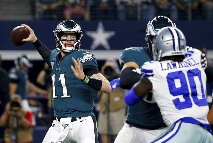 Philadelphia Eagles quarterback Carson Wentz (11) throws a pass under pressure from Dallas Cowboys defensive end Demarcus Lawrence (90) in the first half of an NFL football game in Arlington, Texas, Sunday, Oct. 20, 2019. (AP Photo/Ron Jenkins)
