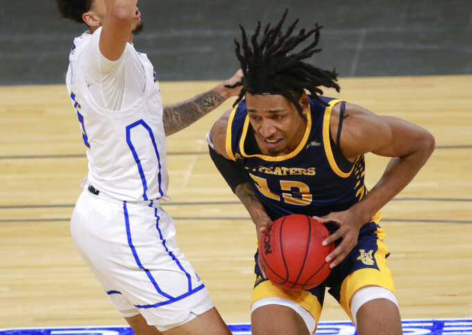 UC Irvine's Austin Johnson (13) is defended by UC Santa Barbara's Miles Norris (5) during the first half of an NCAA college basketball game for the championship of the Big West Conference men's tournament Saturday, March 13, 2021, in Las Vegas. (AP Photo/Ronda Churchill)