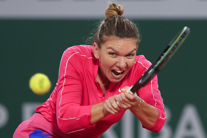 FILE - In this file photo dated Sunday, Oct. 4, 2020, Romania's Simona Halep plays a shot against Poland's Iga Swiatek in the fourth round match of the French Open tennis tournament at the Roland Garros stadium in Paris, France.  Simona Halep said Saturday Oct. 31, 2020, that she has tested positive for COVID-19 coronavirus. (AP Photo/Michel Euler, FILE)