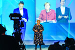 Norway's Prime Minister Erna Solberg stands on stage, with online screen image of German Chancellor Angela Merkel, centre behind, during the official opening of the NordLink, the first power connection between Norway and Germany. (Gorm Kallestad / NTB via AP)