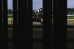 Horses and riders are seen through a fence during workouts at Belmont Park in Elmont, N.Y., Friday, June 19, 2020. The Belmont Stakes is scheduled to run on Saturday. (AP Photo/Seth Wenig)