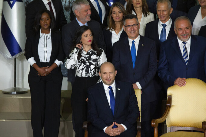 Israeli Prime Minister Naftali Bennett, seated, smiles as he waits to pose for a group photo with the ministers of the new government at the President's residence in Jerusalem, Monday, June 14, 2021. (AP Photo/Maya Alleruzzo)