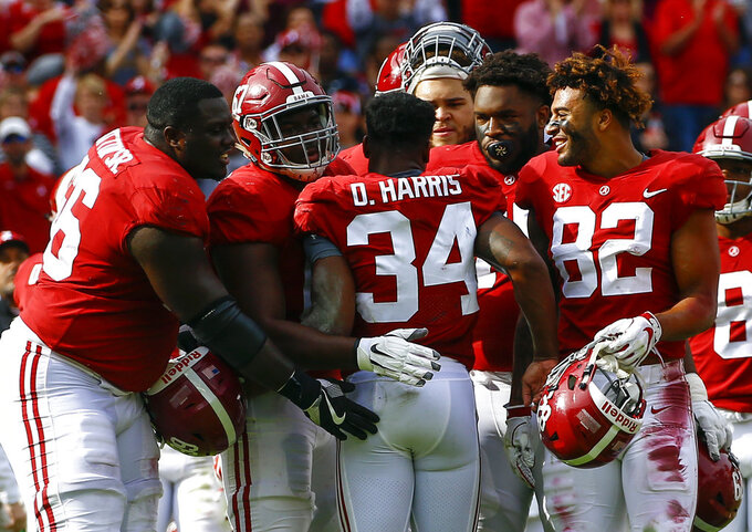 Alabama running back Damien Harris (34) is greeted by teammates after being shaken up on a play during the second half of an NCAA college football game against Citadel, Saturday, Nov. 17, 2018, in Tuscaloosa, Ala. (AP Photo/Butch Dill)