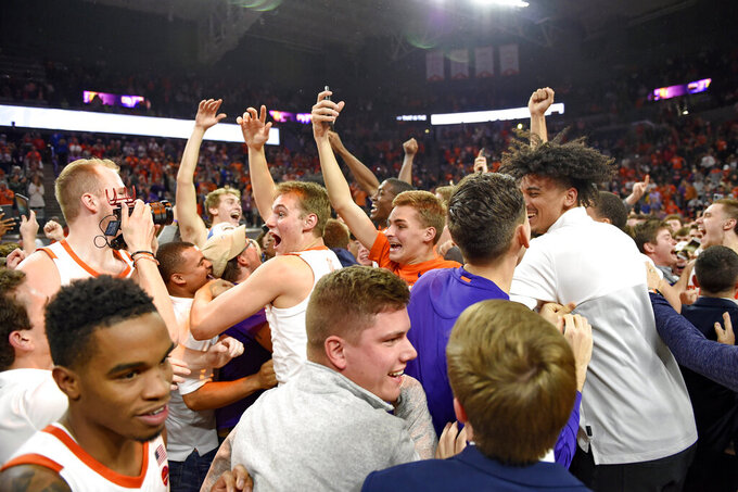 Clemson players and fans celebrate after an NCAA college basketball game against Duke Tuesday, Jan. 14, 2020, in Clemson, S.C. Clemson won 79-72. (AP Photo/Richard Shiro)