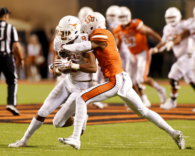 Oklahoma State cornerback A.J. Green, right, tackles Texas wide receiver Collin Johnson in the second half of an NCAA college football game in Stillwater, Okla., Saturday, Oct. 27, 2018. (AP Photo/Brody Schmidt)